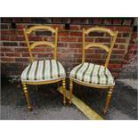 A pair of French gilt wood parlour chairs, upholstered seats on turned and fluted front legs