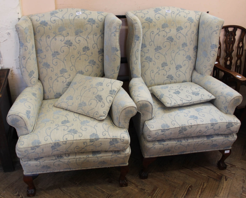 Lot 1048 - A pair of pale blue floral upholstered wingback chairs with oak claw and ball feet