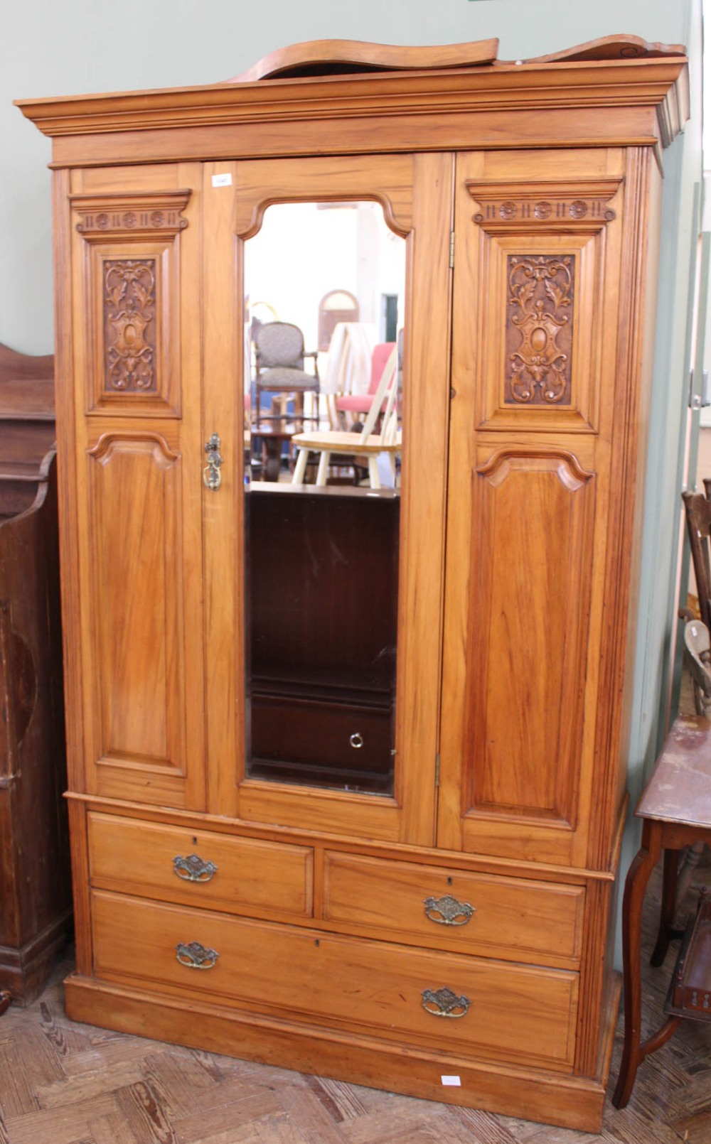 Lot 1040 - An Edwardian satinwood carved double wardrobe with three drawers below