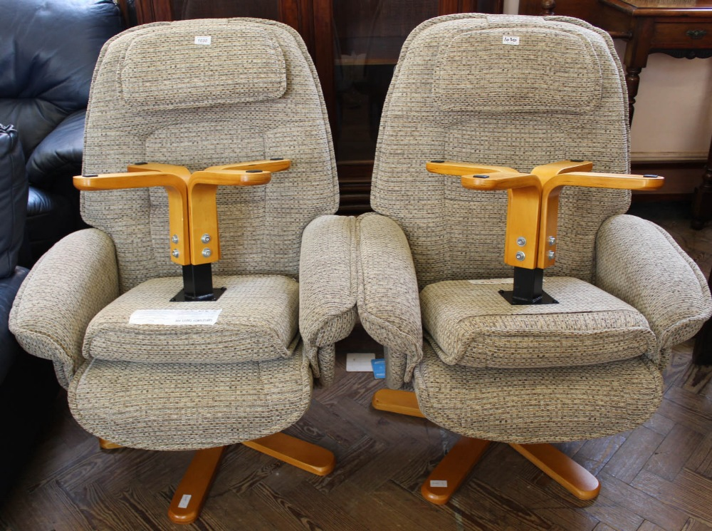 Lot 1030 - A pair of Relaxateeze recliners with beige upholstery and matching footstools