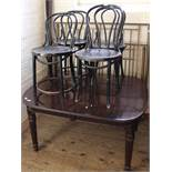 A set of four black painted bentwood cafe chairs and a mahogany dining table with reeded legs