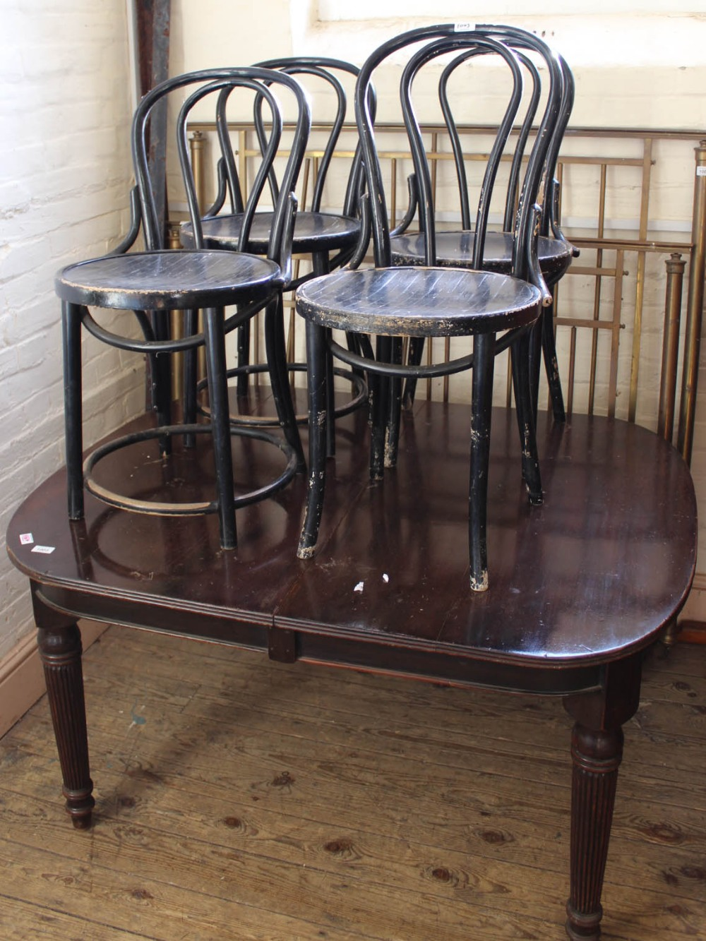 Lot 1003 - A set of four black painted bentwood cafe chairs and a mahogany dining table with reeded legs