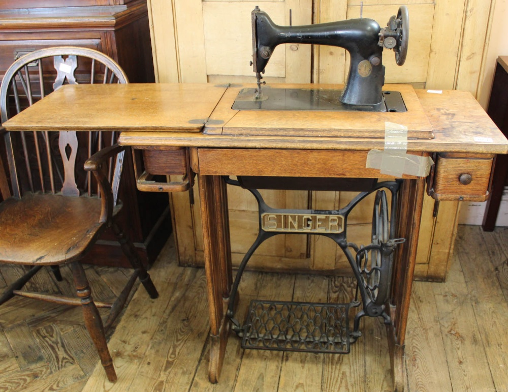 Lot 1054 - An oak Singer sewing machine with treadle,