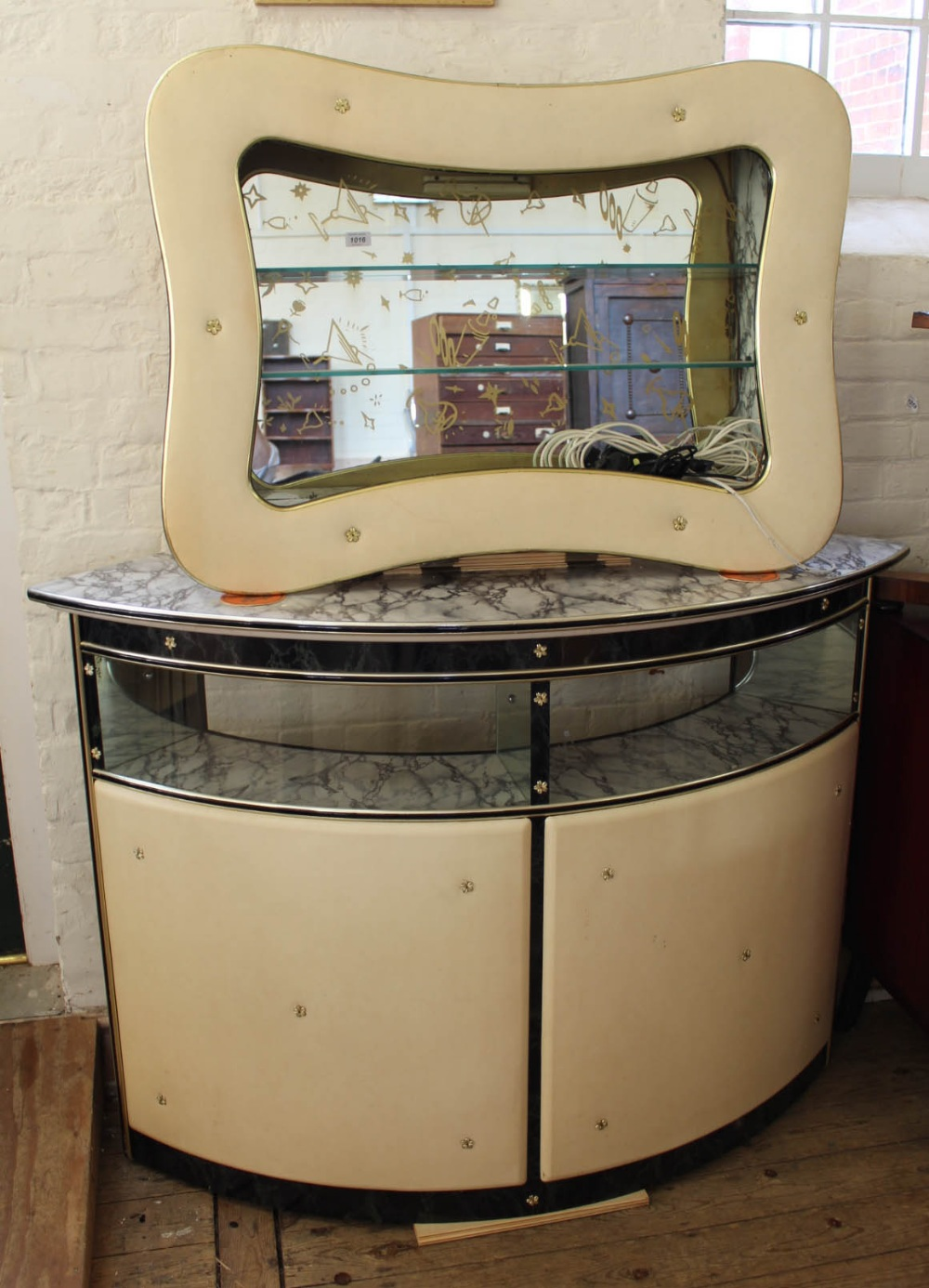 Lot 1016 - A 1950's white vinyl and glass mini bar with matching mirror and glass wall mounted shelving unit