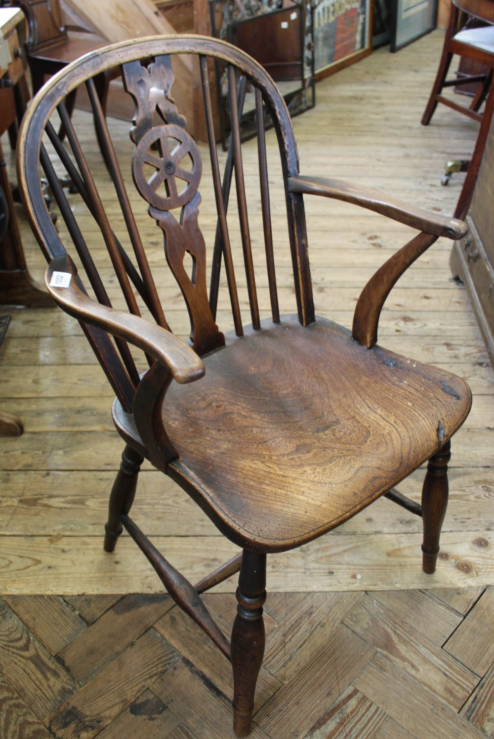 Lot 1052 - A 19th Century elm seat wheelback chair