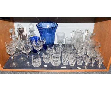 A quantity of cut lead crystal including a part suite of Waterford drinking glasses, decanters and two blue glass vases (one
