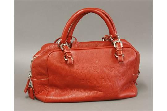A Prada Red Leather Handbag With Embossed Milano Logo Design Cream Fabric Lining And
