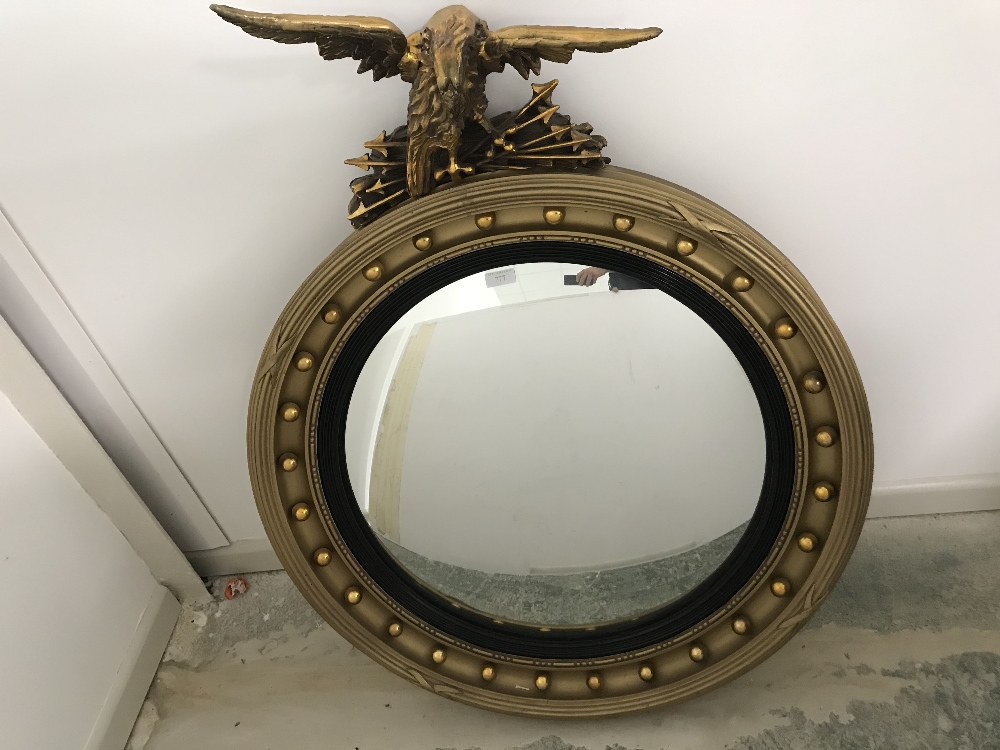 Lot 777 - Circular convex Regency gilt mirror with eagle finial 102cm overall height
