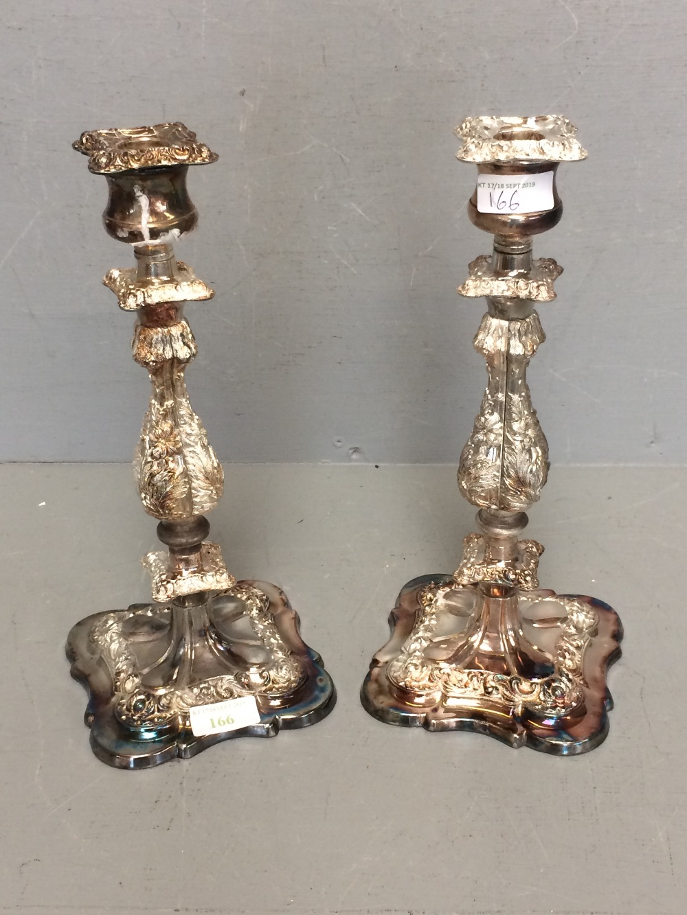 Lot 166 - Pair of white metal candle sticks with floral decoration 30.5cm