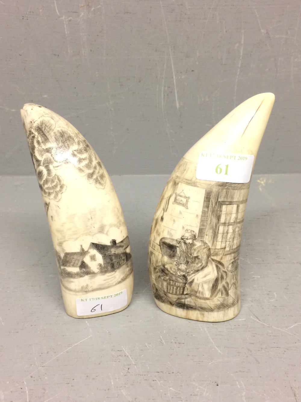 Lot 61 - Pair of walrus scrimshaw worked tusks (16 cm), 1 decorated with a cottage & the other with a