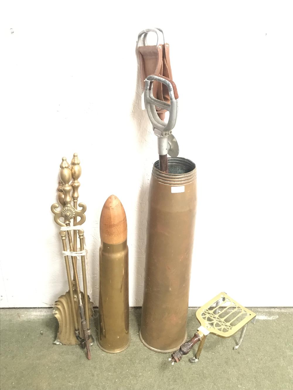Lot 245 - Large (64 x 16cm) brass shell case, 2 shooting sticks, fire irons & a trivet. 1917 shell case (42cm)