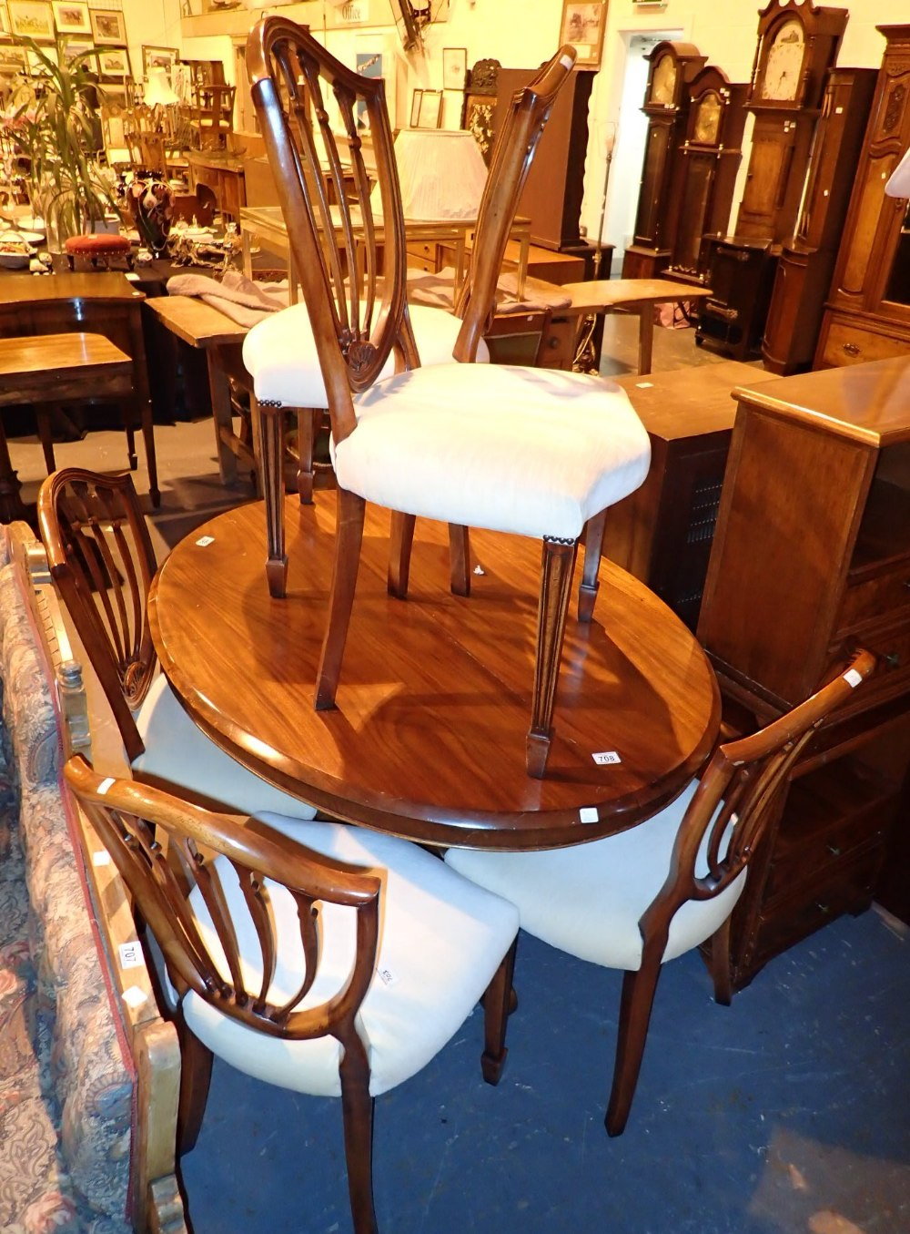 Mahogany tilt top breakfast table on tripod base with six modern upholstered shield back dining