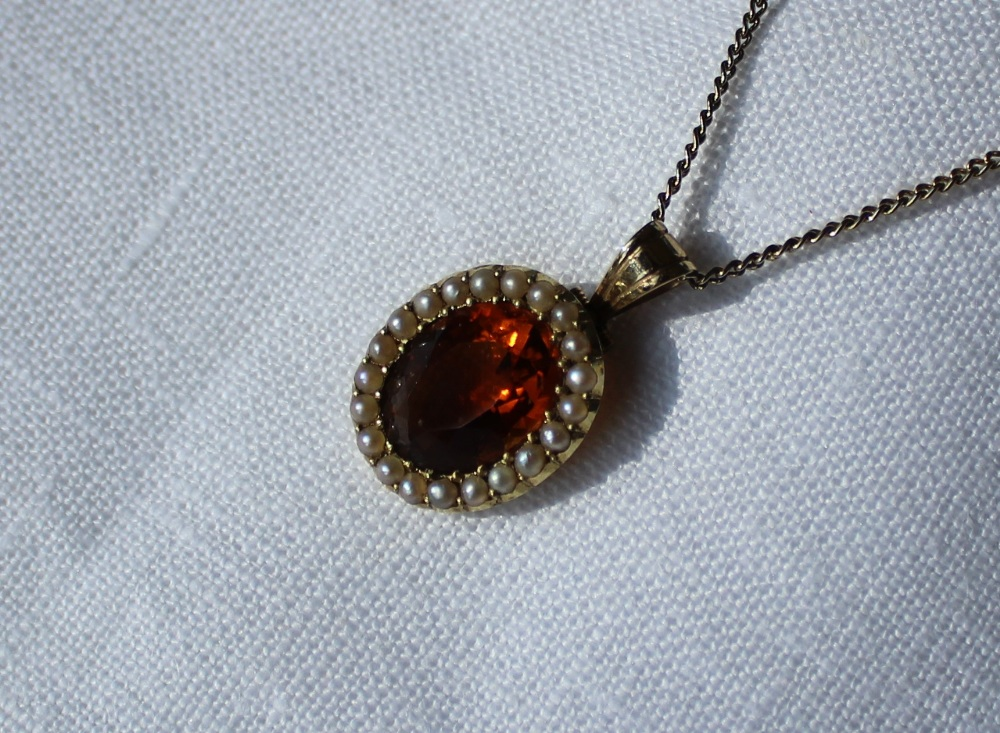 Lot 29 - A 15ct gold citrine and seed pearl pendant set with an oval faceted citrine surrounded by seed