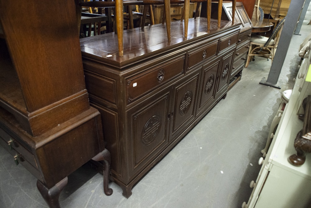 Lot 58 - AN ORIENTAL DARK WOOD SIDEBOARD, THREE DRAWERS ABOVE THREE DOORS WITH DECORATIVE CARVED PANELS