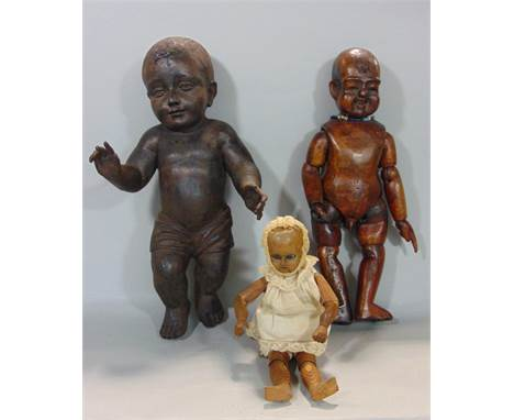 Carved stained soft wood figure of a standing child wearing a loin cloth, 38 cm high, together with a further Eastern hardwoo