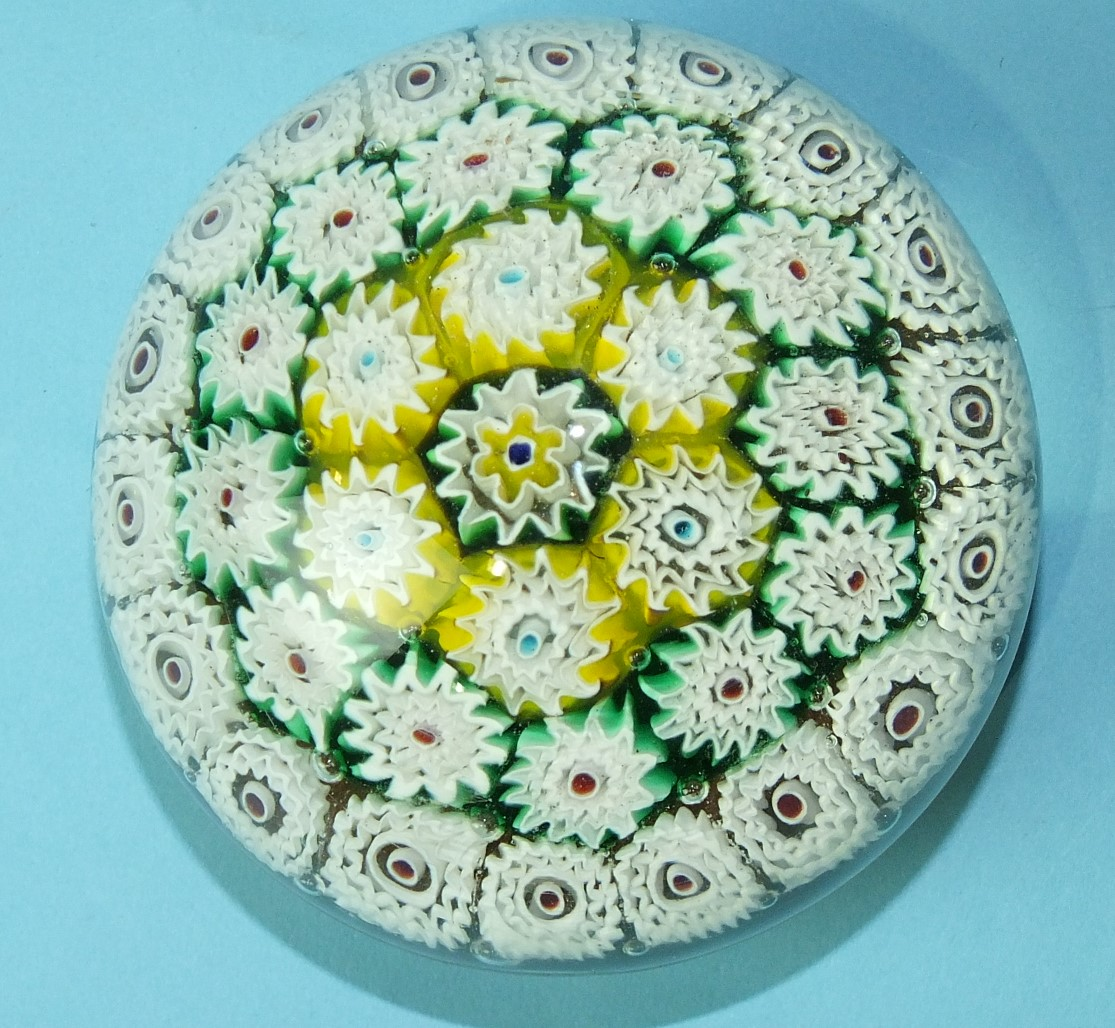 Lot 229 - A large glass paperweight with an arrangement of concentric multi-coloured canes, 10cm diameter.