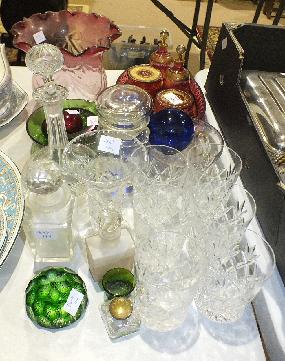 Lot 144 - A four-piece cranberry glass dressing table set, on oval tray with white enamel and gilt decoration,