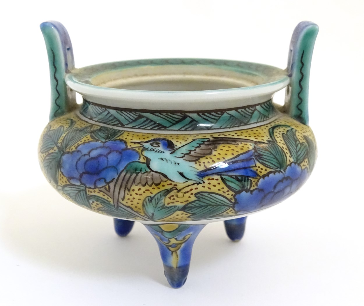 Lot 25 - A Chinese three legged, two handled censer, decorated with a bird and flowers.