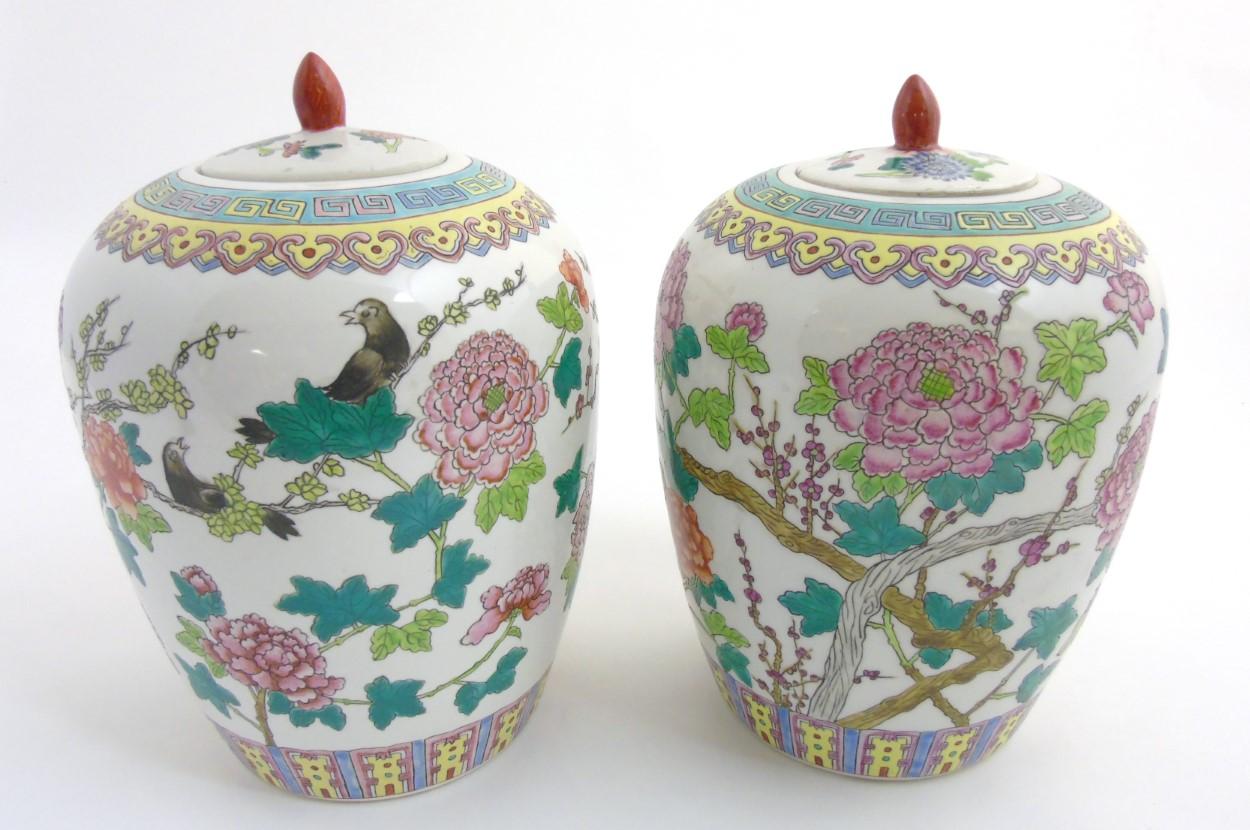 Lot 11 - A pair of Famille Rose lidded vases / ginger jars of ovoid form,