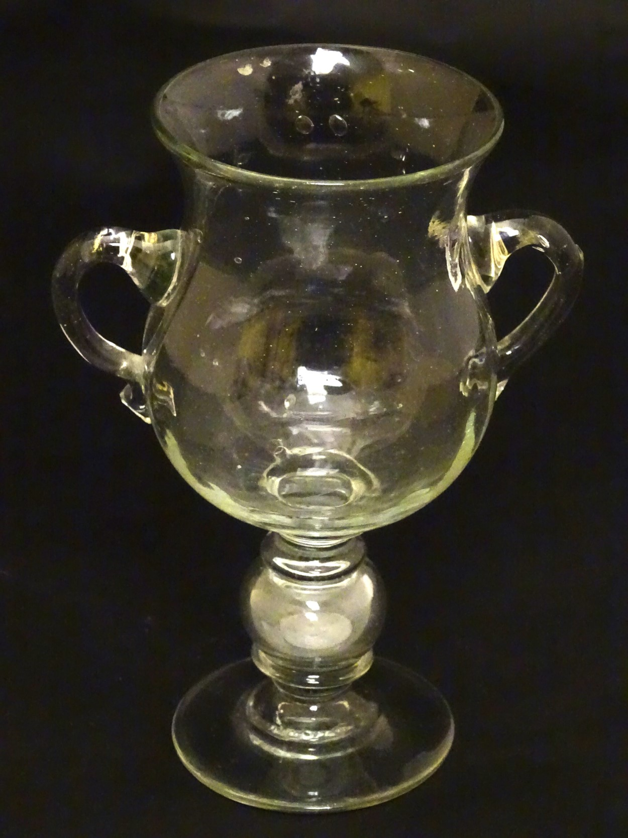 Lot 114 - Pedestal glass with coin : a two handled pedestal early 20 th C glass having a ground pontil scar,