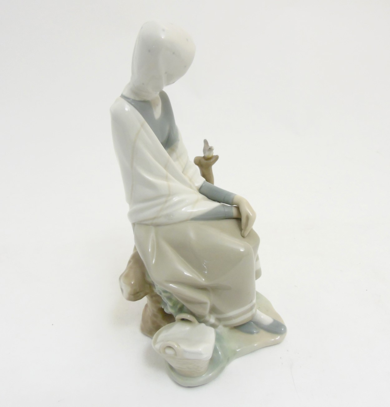 Lot 75 - A Lladro 'New Shepherdess' figurine of a girl sat watching a bird, makers mark to base,