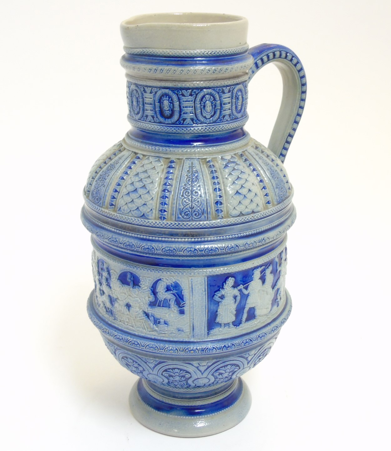 Lot 65 - A German Westerwald style salt glazed ewer jug with molded relief of folklore scenes and other