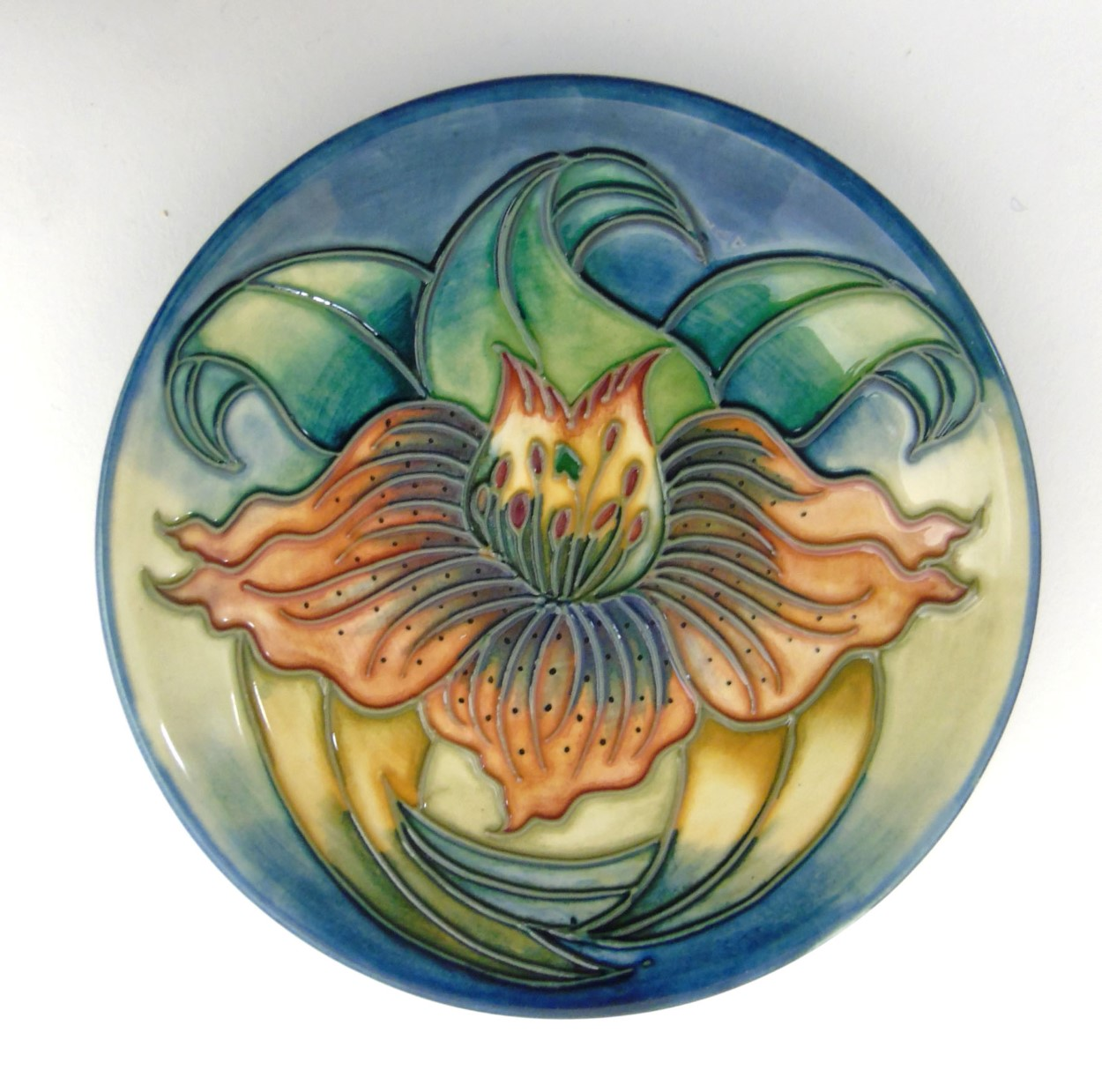 Lot 69 - A small Moorcroft Anna Lily plate depicting an orange tiger lily designed by Nicola Slaney.