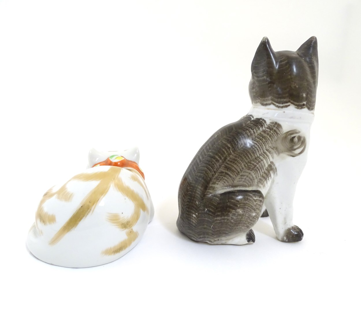 Lot 80 - Two ceramic models of cats, one seated, one recumbent. Height of the seated model: approx.