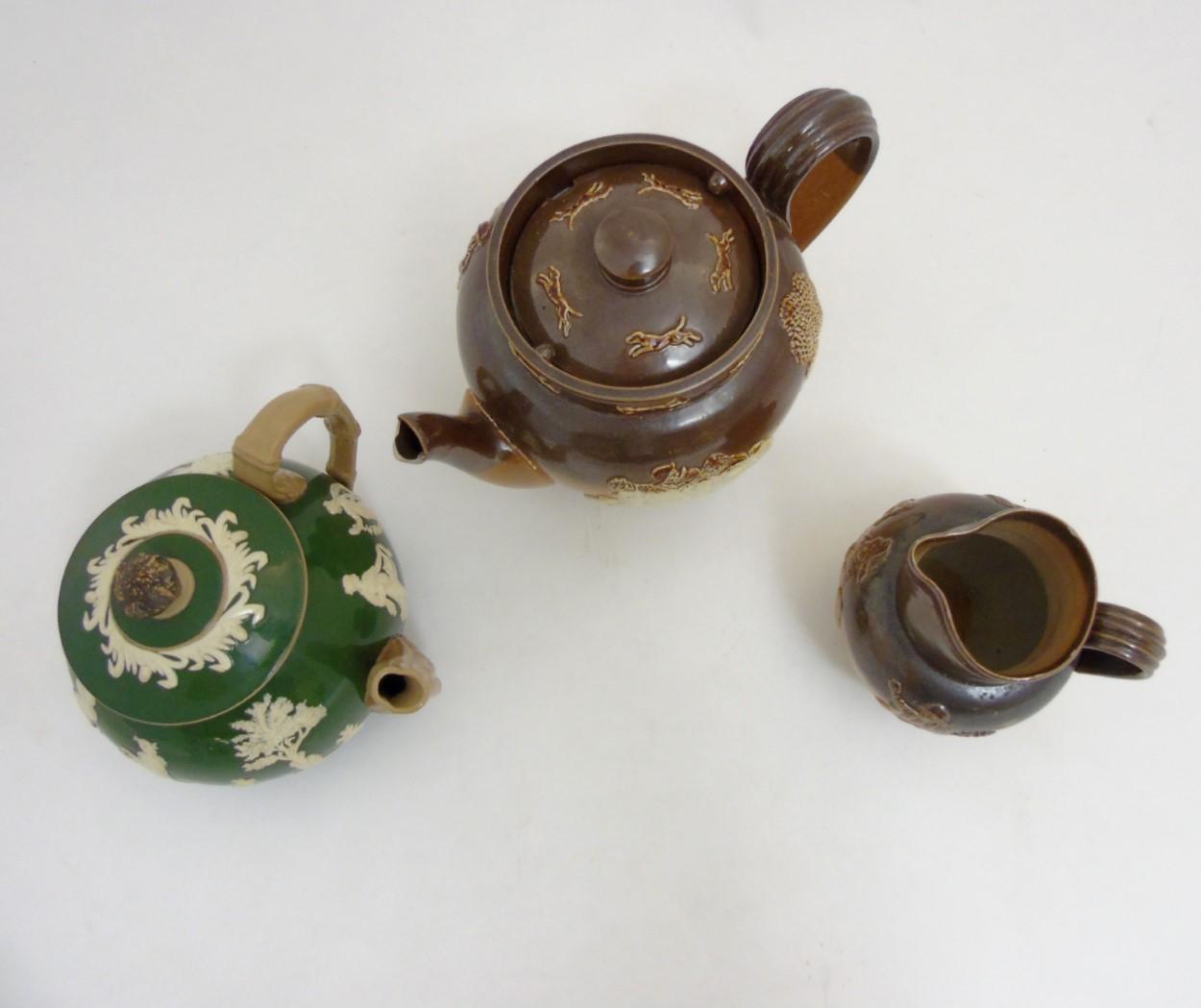 Lot 61 - Three pieces of stoneware ceramics comprising a Royal Doulton salt glazed hunting teapot,