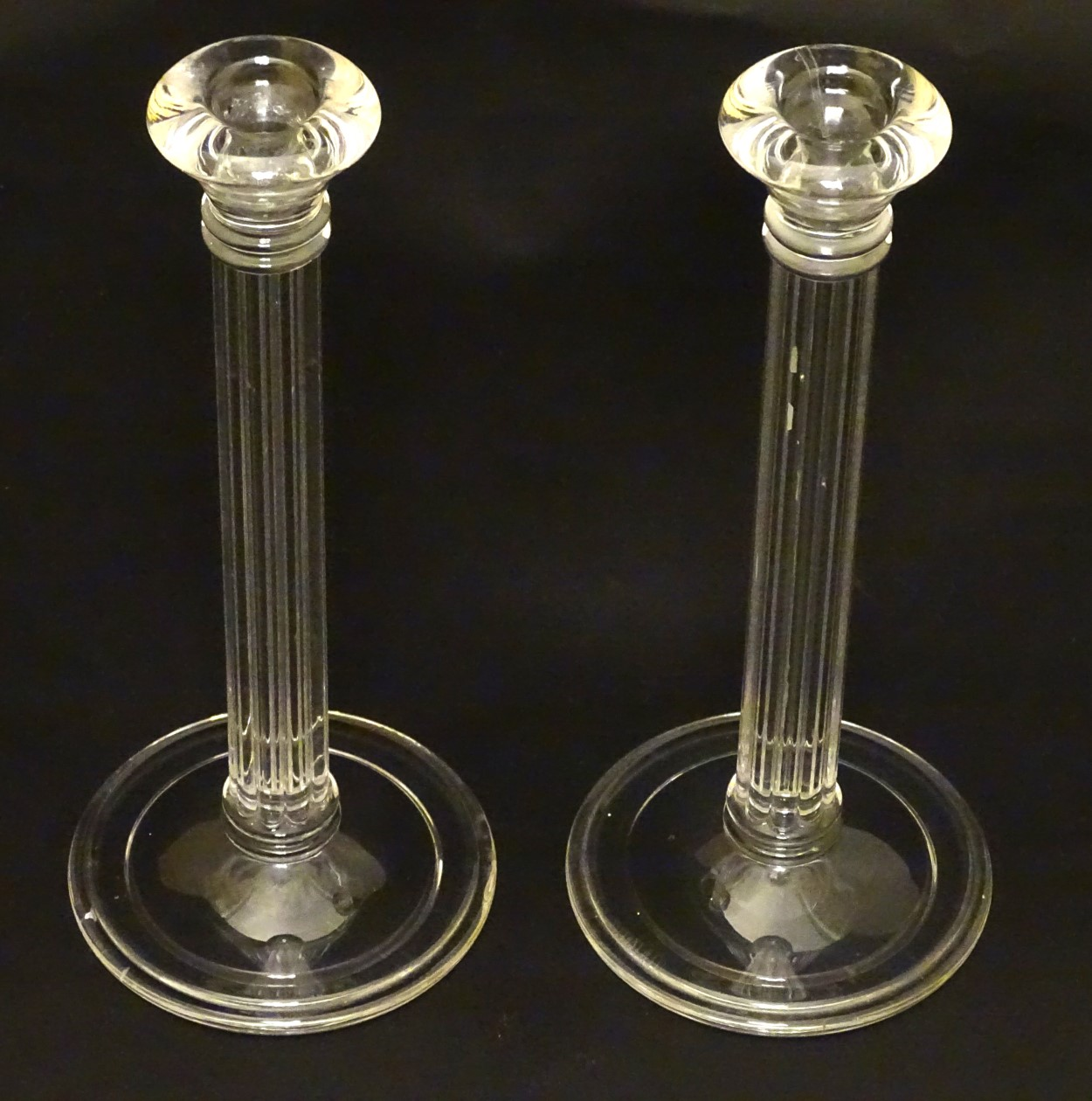 Lot 100 - Tiffany & Co: A pair of pedestal glass candlesticks with receded columns ,
