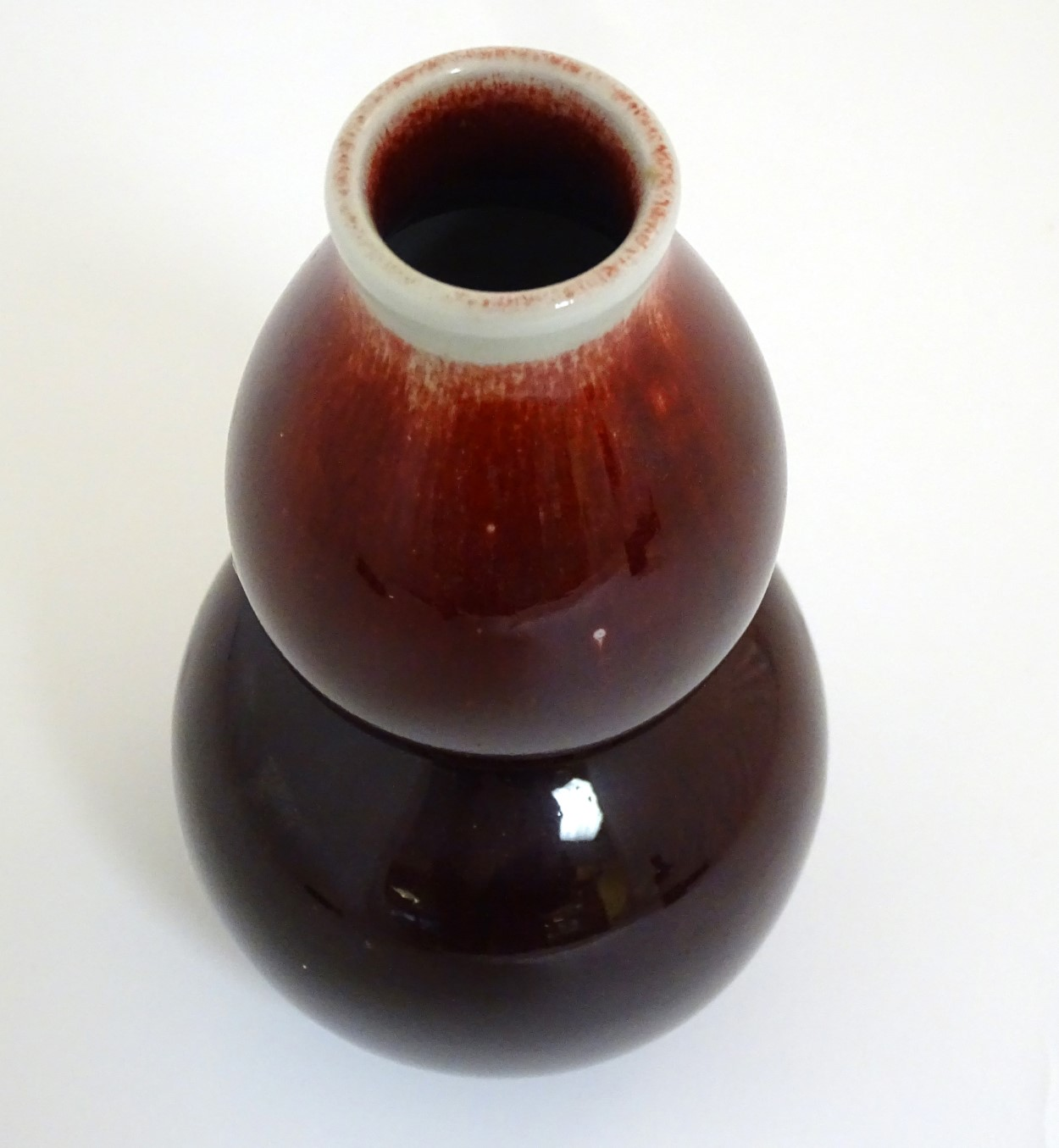 Lot 2 - A Chinese sang-de-boeuf double gourd, high fired porcelain vase. Indistinct Chinese marking to base.