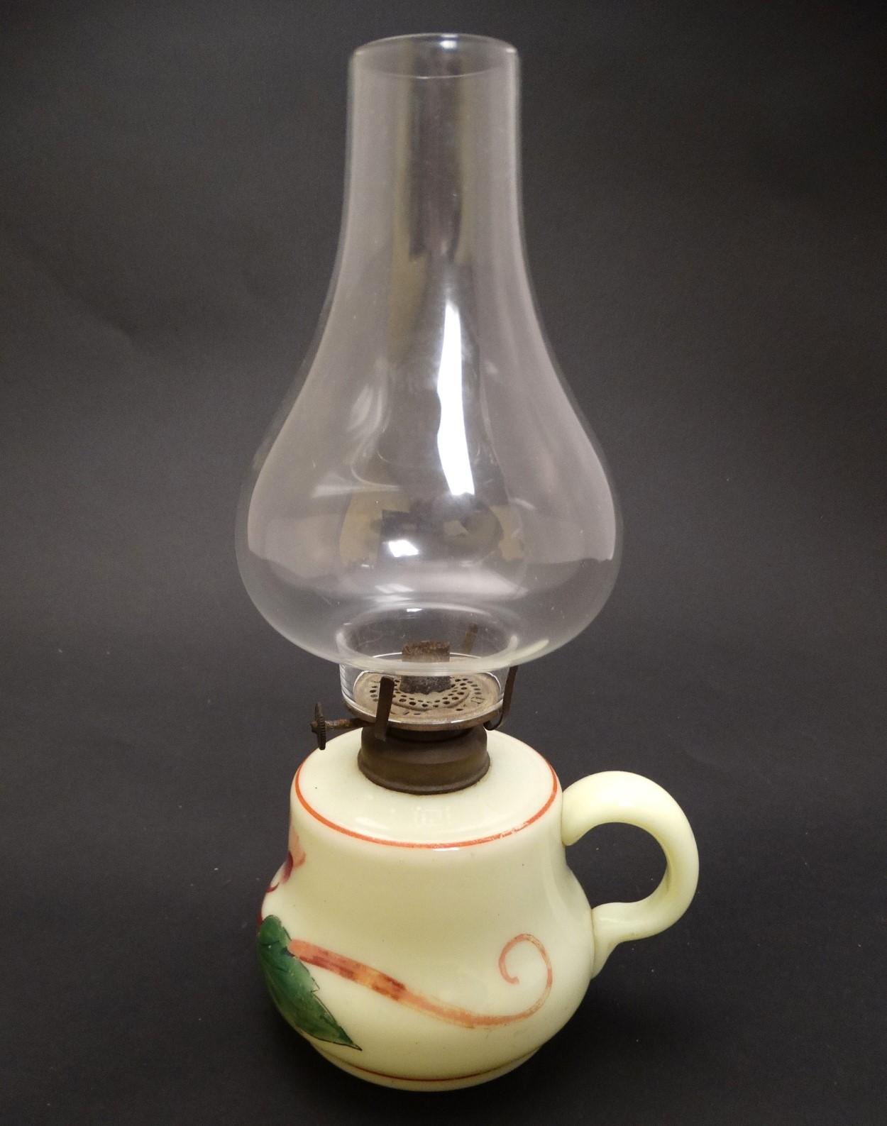 Lot 110 - A small glass oil lamp with floral decoration, loop handle and clear glass chimney.