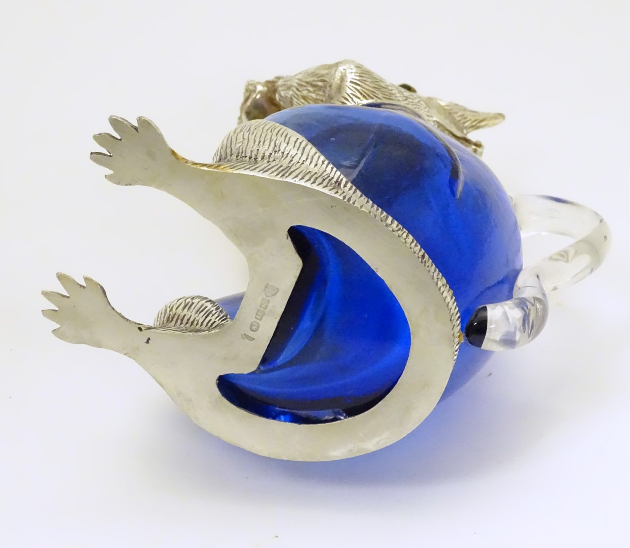 Lot 108 - Glass : a 21 st C blue glass and silver plate claret jug in the form of a squirrel eating a nut ,
