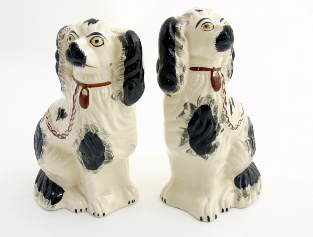 Lot 56 - Two Victorian Staffordshire spaniels, with black patch decoration and brown lock and chain,