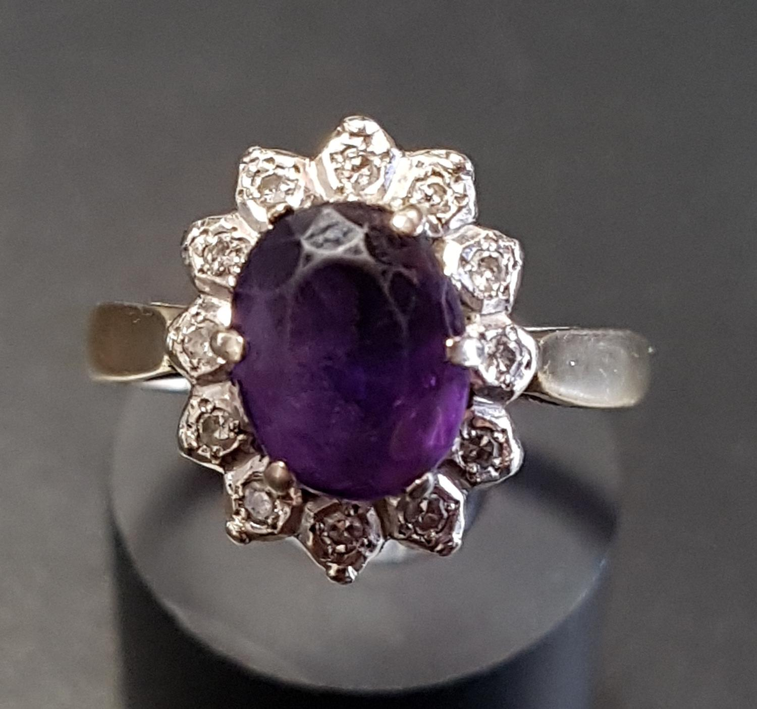 Lot 58 - AMETHYST AND DIAMOND CLUSTER RING the central oval cut amethyst in surround of twelve illusion set