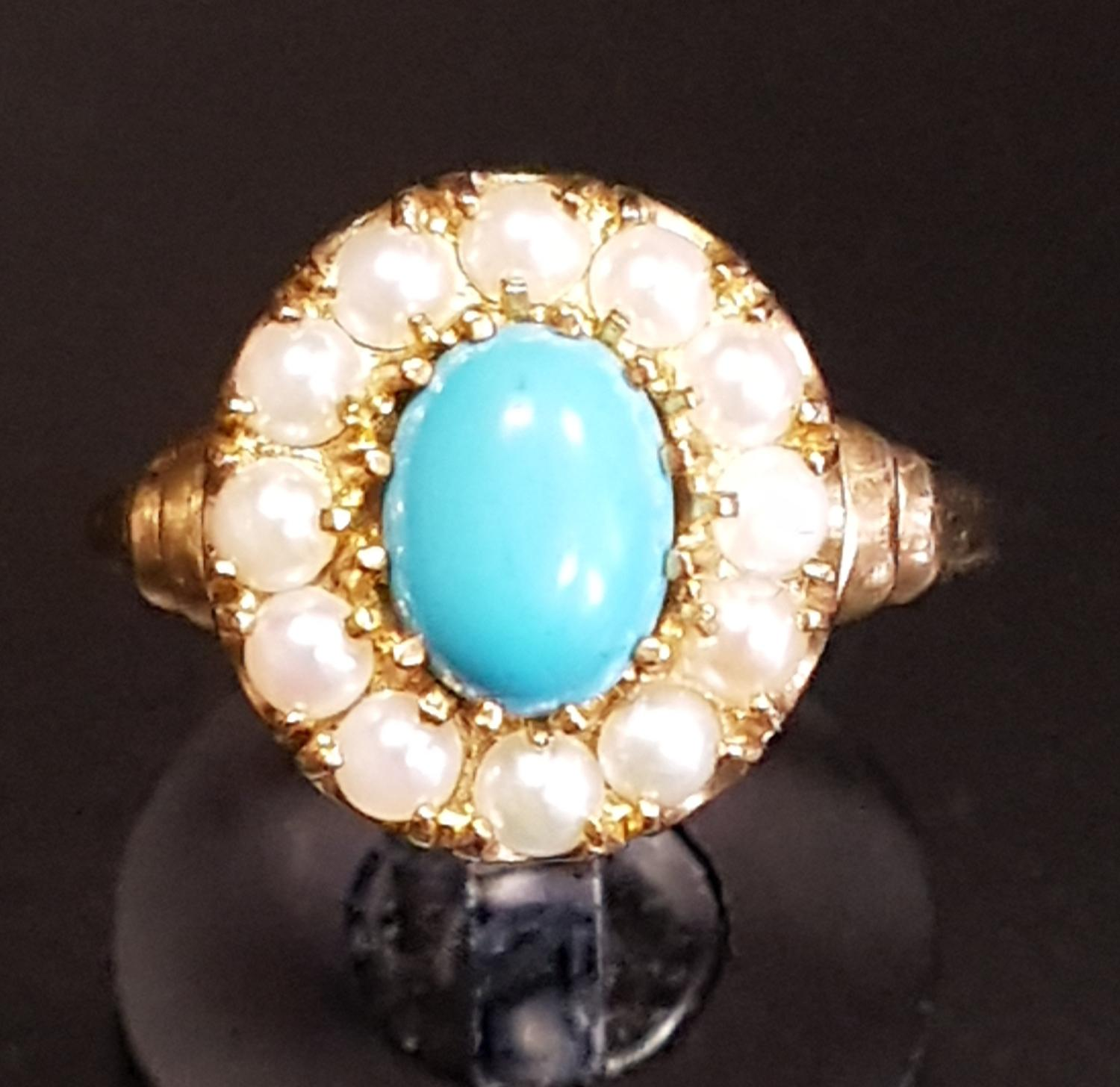 Lot 16 - TURQUOISE AND SEED PEARL CLUSTER RING the central oval cabochon turquoise stone in twelve pearl