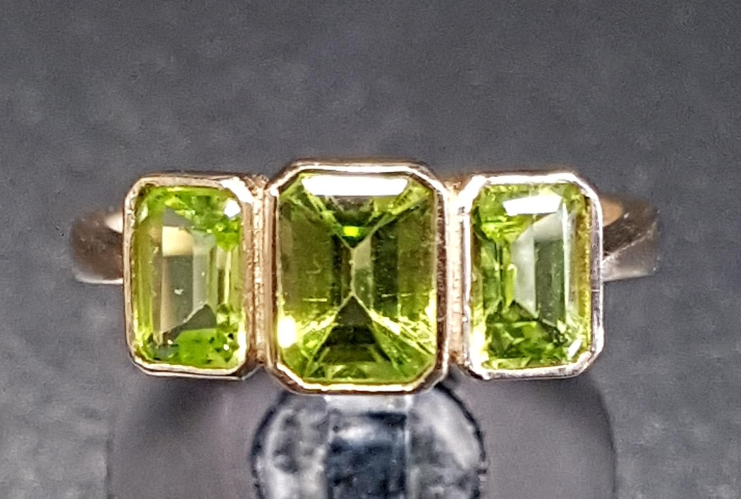 Lot 9 - GRADUATED PERIDOT THREE STONE RING the emerald cut peridots in bezel settings, on nine carat gold