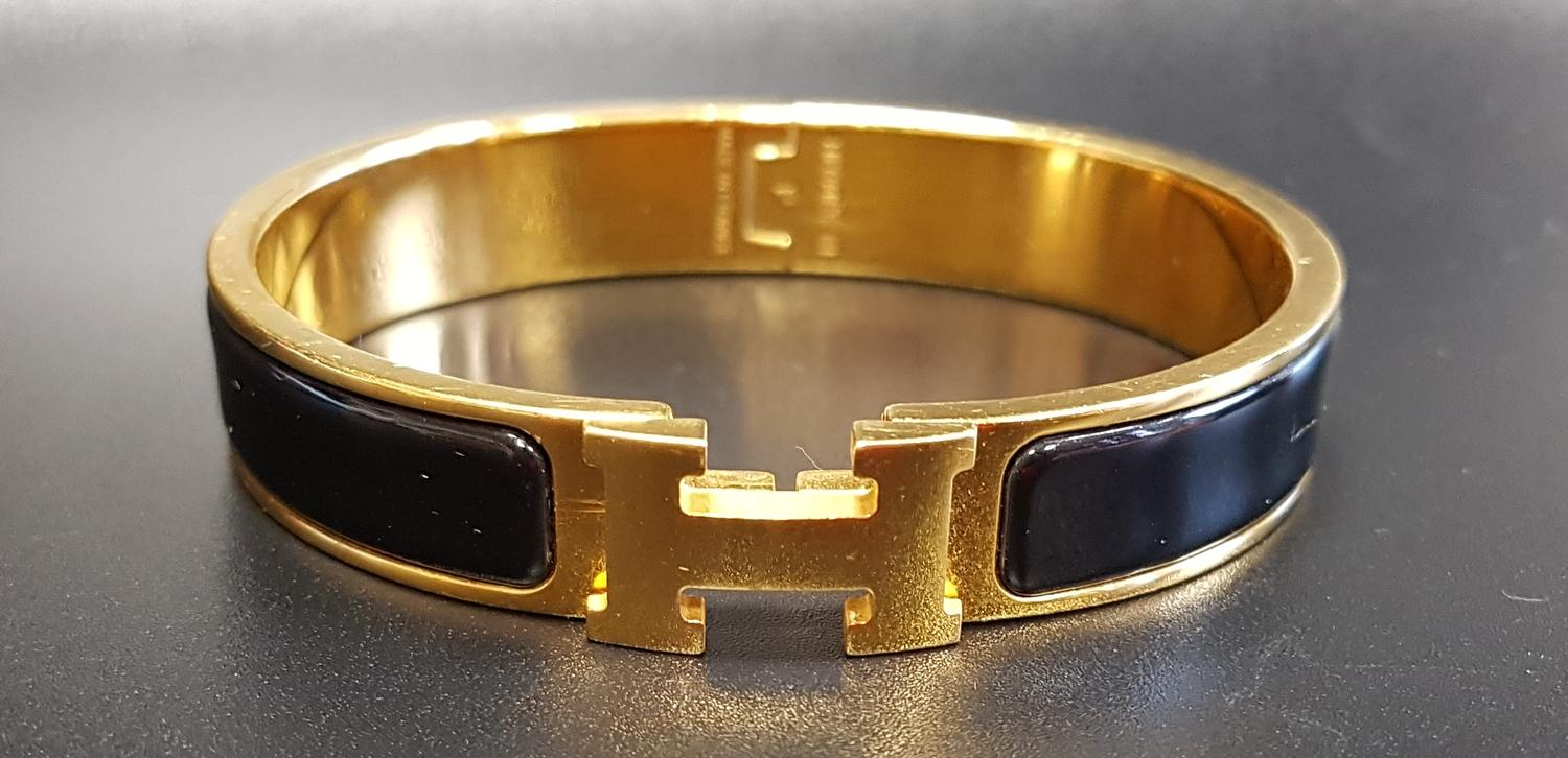 Lot 57 - HERMÉS CLIC H BRACELET the hinged bangle with black enamel decoration
