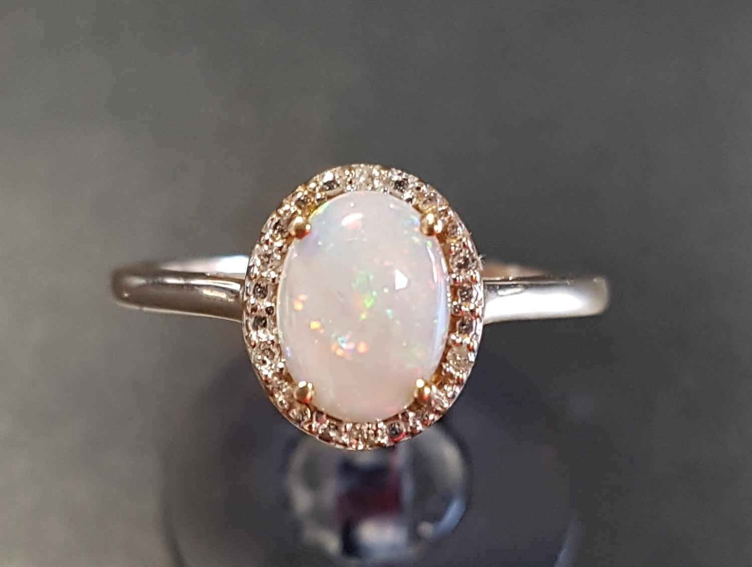 Lot 29 - OPAL AND DIAMOND CLUSTER RING the central oval opal in diamond surround, on nine carat gold shank,
