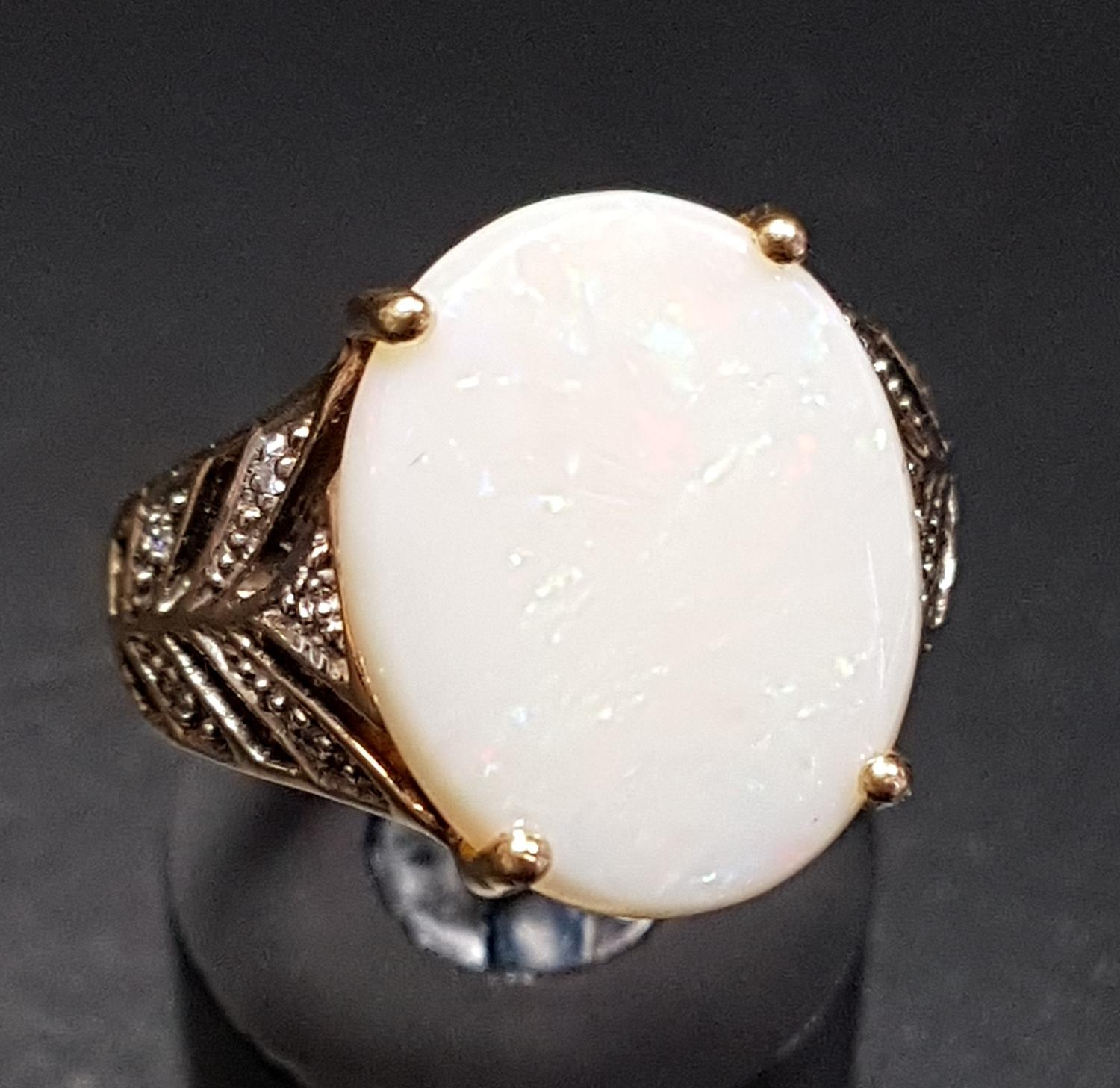 Lot 45 - OPAL AND DIAMOND DRESS RING the central oval opal flanked by diamond set split shoulders, on nine