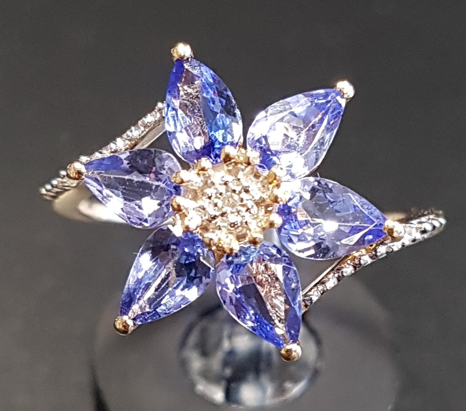 Lot 38 - ATTRACTIVE TANZANITE AND DIAMOND CLUSTER DRESS RING the central diamond surrounded by six pear cut