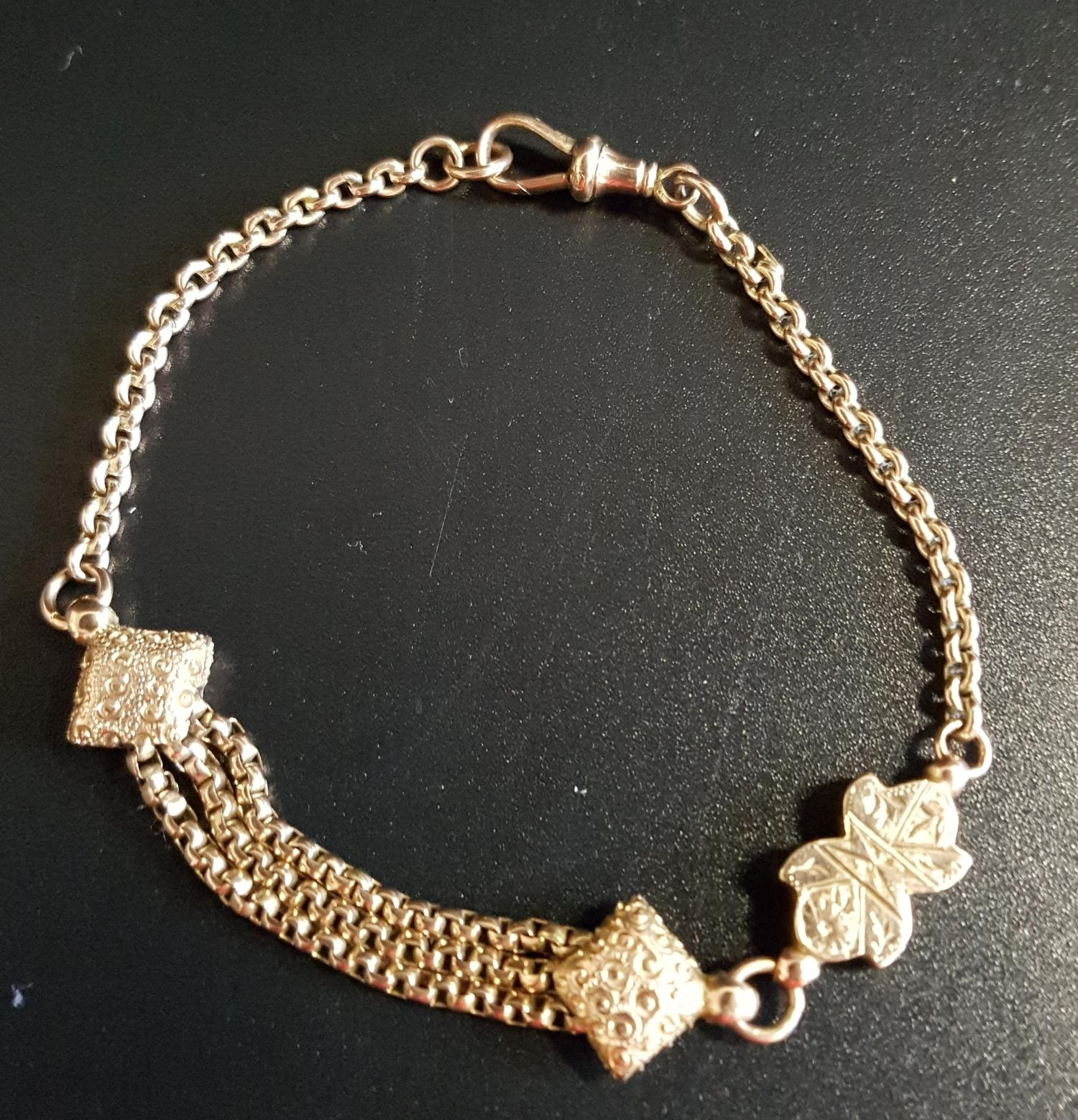 Lot 40 - UNUSUAL NINE CARAT GOLD ALBERTINA BRACELET with central shaped links and triple chain section,