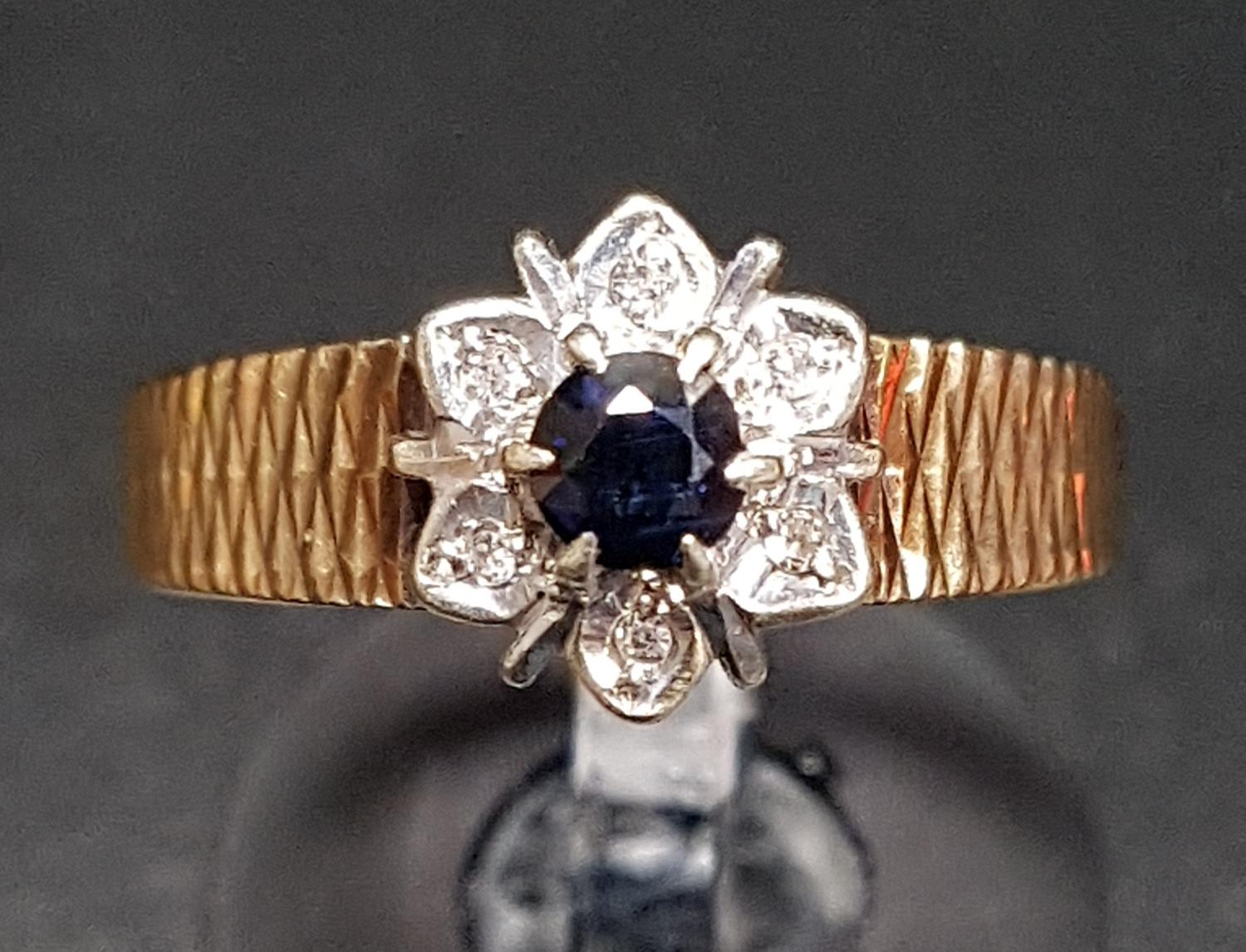 Lot 19 - SAPPHIRE AND DIAMOND FLOWER HEAD DESIGN CLUSTER RING the round cut sapphire in surround of six
