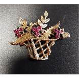 RUBY AND SAPPHIRE NINE CARAT GOLD BROOCH in the form of a basket of flowers, with three ruby and