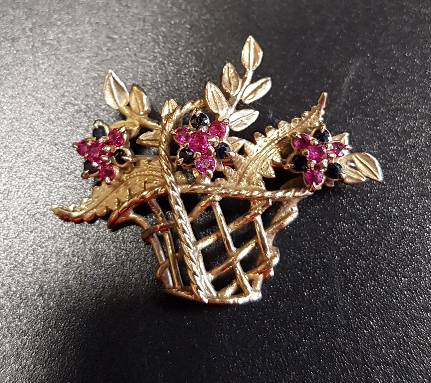 Lot 42 - RUBY AND SAPPHIRE NINE CARAT GOLD BROOCH in the form of a basket of flowers, with three ruby and