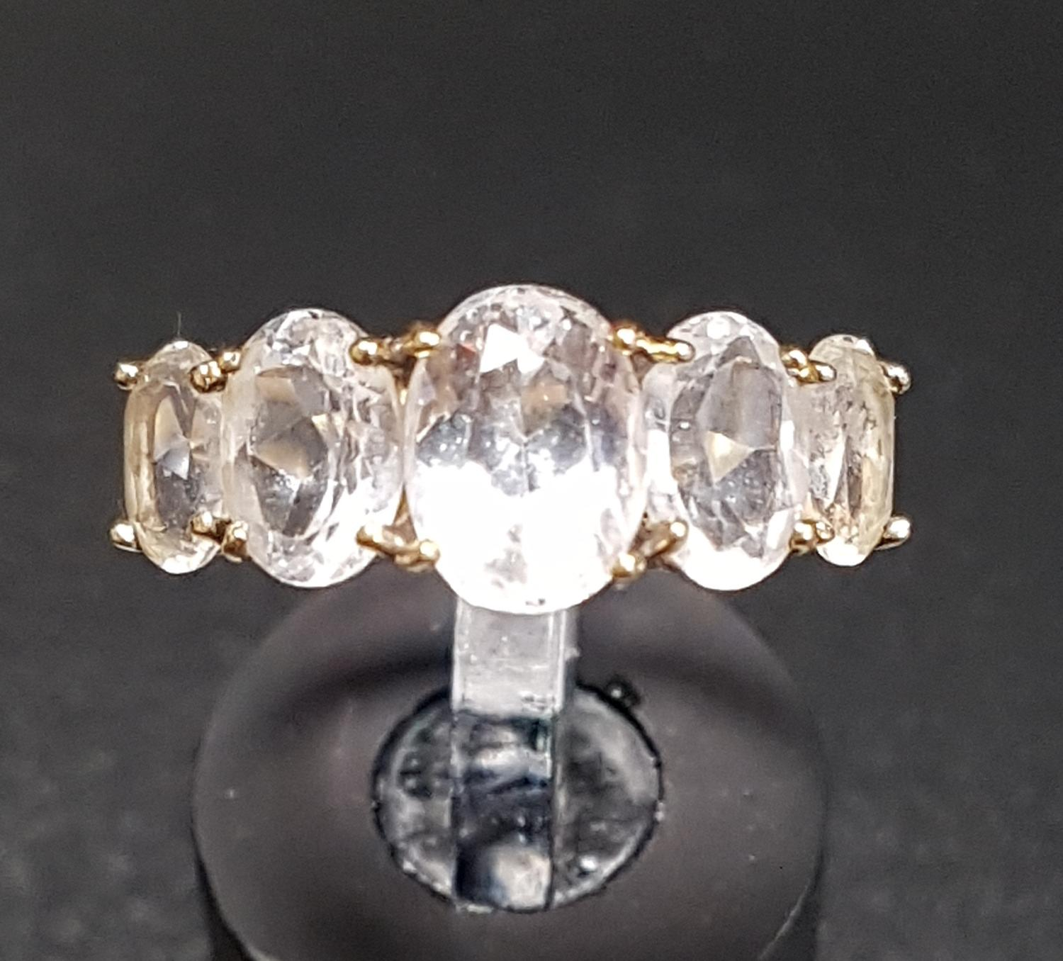 Lot 36 - GRADUATED CLEAR QUARTZ FIVE STONE RING on ten carat gold shank with decorative split shoulders, ring