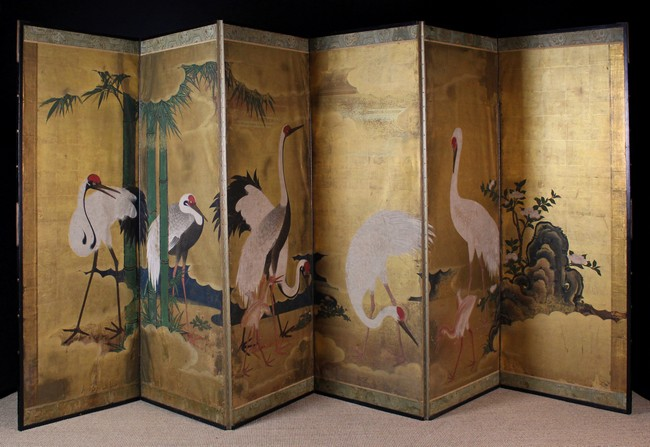 Lot 57 - A 19th Century Japanese Six-fold Screen hand-painted with wading storks amidst rockwork and bamboo,