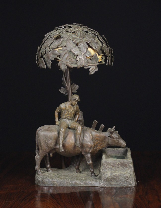 Lot 8 - A Bronze Patinated Spelter Occasional Lamp modelled with a man sat upon a cow at water trough,