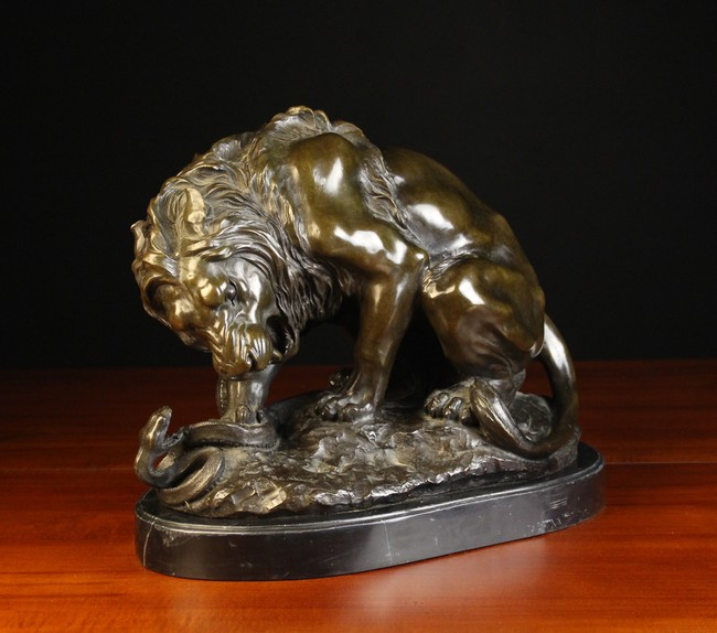 Lot 4 - A Brown Patinated Bronze Study of a Lion and Snake on a naturalistic base signed B.C.