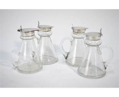 A set of three conical glass whisky noggins with star-cut bases and silver tops with trefoil thumb-pieces, John Grinsell & So